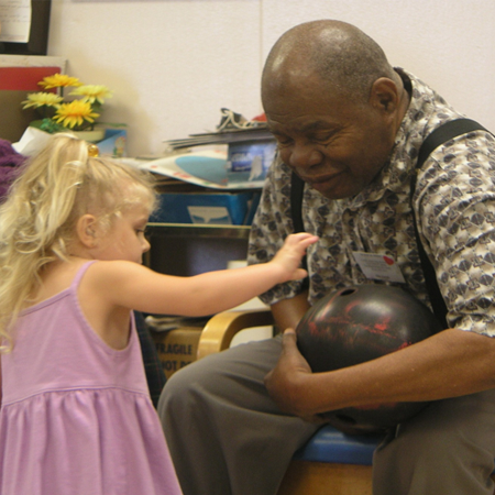 Intergenerational, little girl with older gentlemen playing with a bowling ball