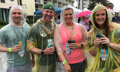 Ocean Brews event, 4 people in rain gear holding their glasses up