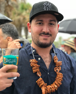 Ocean Brews event closeup of man with pretzel necklace holding glass with beer